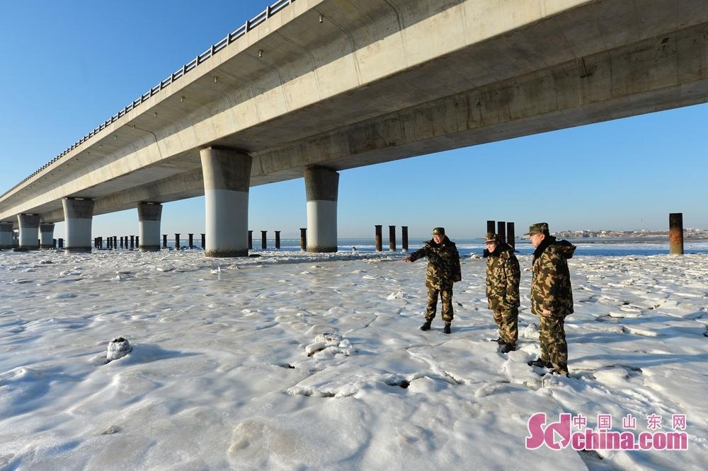 <br/><br/>  2018年1月12日,青岛边防支队红岛边防派出所民警在胶州湾跨海大桥下查看冰情。<br/>