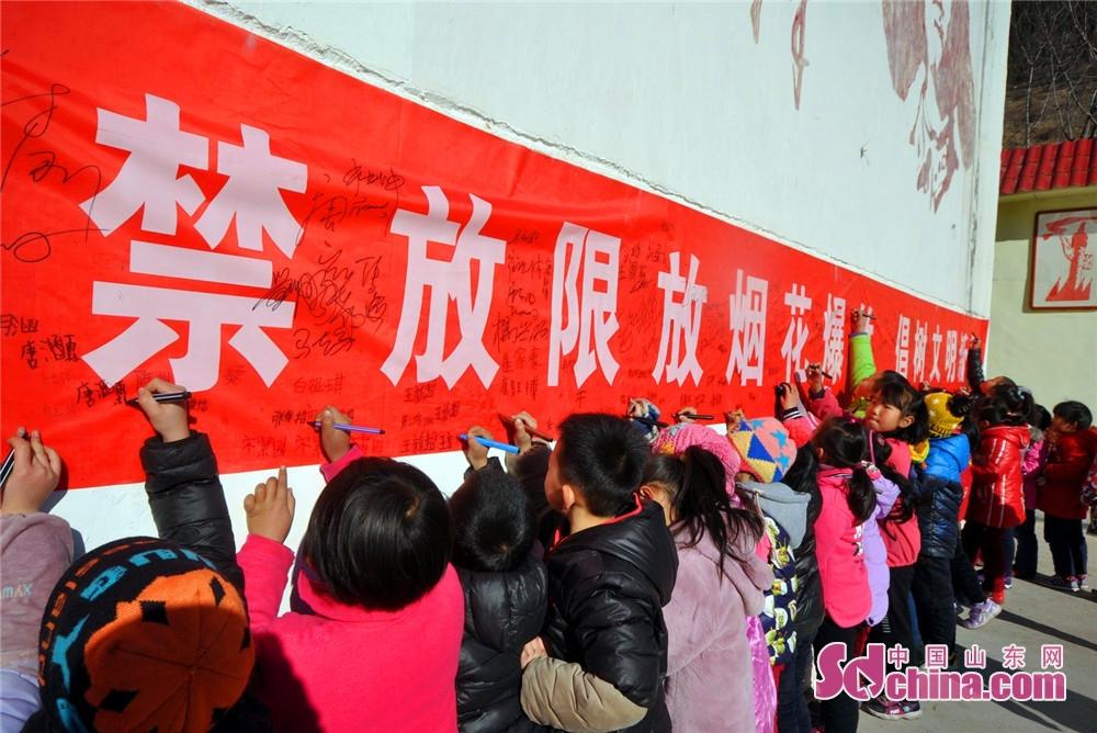 <br/>  沂源县南鲁山镇中心小学的小学生在禁放或限放烟花爆竹倡议上签名。
