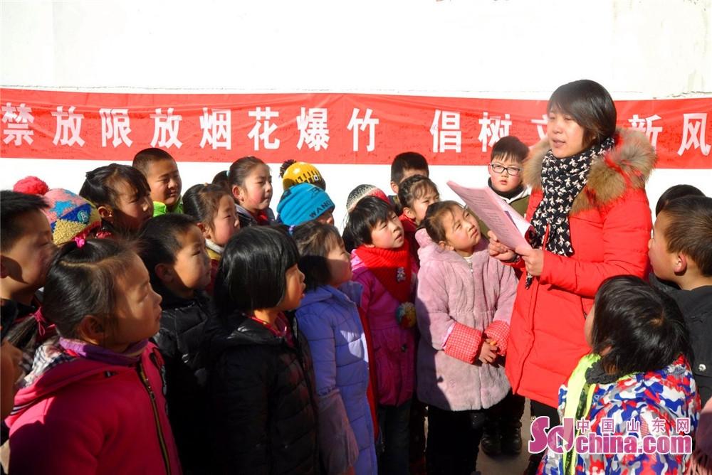 <br/>  沂源县南鲁山镇中心小学的老师向小学生宣传禁放或限放烟花爆竹倡议。