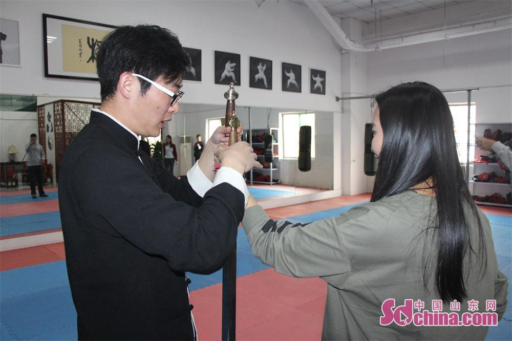 Zhang Zhengli, 20th inheritor of Chen-style Tai Chi, teaches a foreigner about the correct sword holding method. Four foreign students that learn in Shandong University arrived at Jinan Zhengli Chen-style Taijiquan Club recently to study Taiji Sword, one of the important versions of Tai Chi. (Sdchina.com/Nie Dan)<br/>