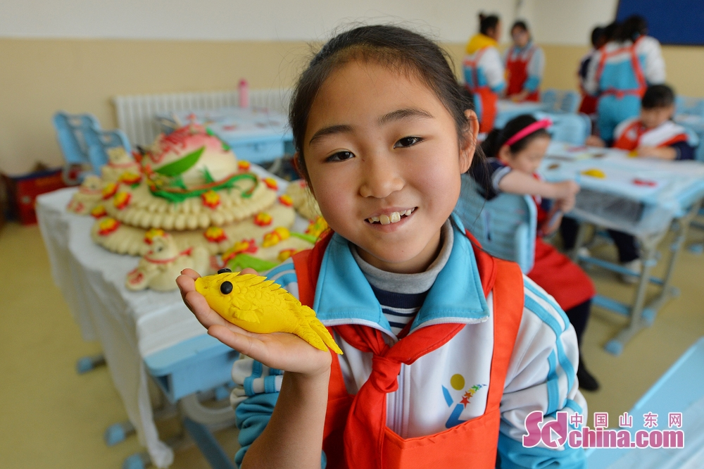 A pupil displays the dough sculpture made by herself in Qingdao, east China's Shandong Province. (Sdchina.com/Wang Haibin)<br/>