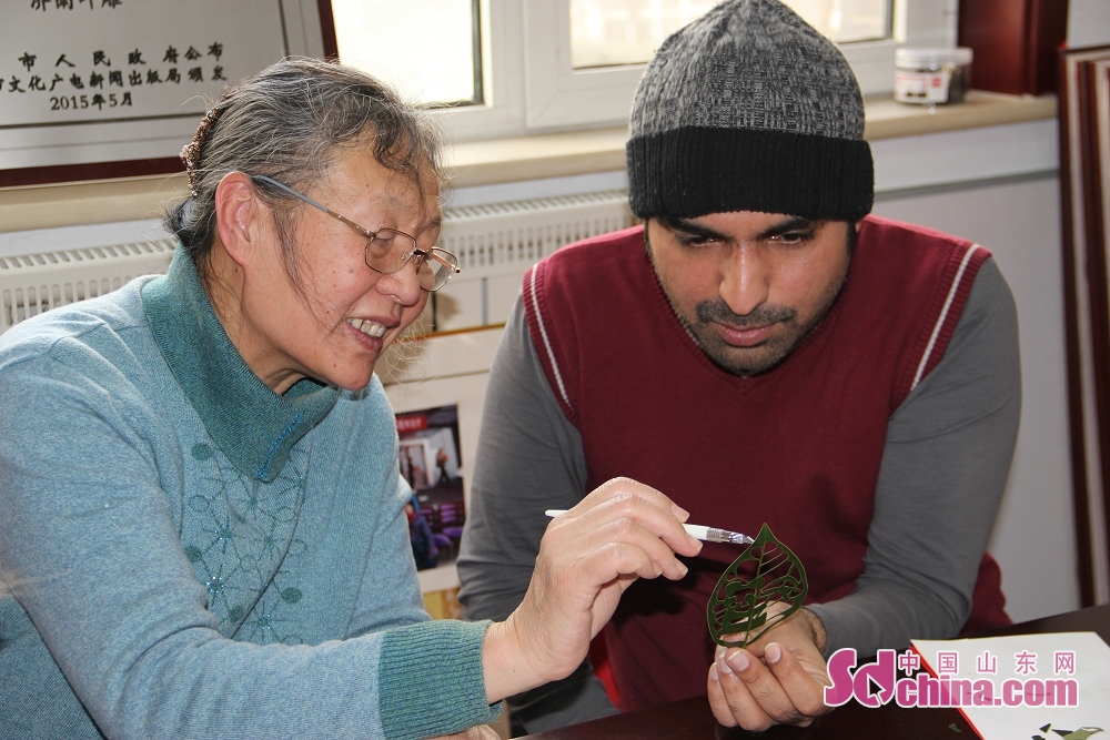 Du Wanli teaches a foreigner how to create leaf carving. Recently, three foreigners went to the studio of Du Wanli, famous leaf carving artist, at the invitation of &amp;ldquo;Touch Shandong&amp;rdquo; column of Sdchina.com to learn leaf carving.(Sdchina.com/Jiao Jingsai)<br/>
