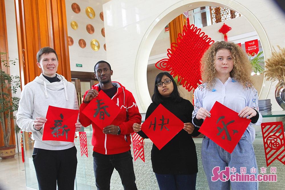 <br/>  1月30日,在威海南海新区江南城小区举办的&amp;ldquo;喜迎新年写春联,情暖居民送祝福&amp;rdquo;活动中,外国留学生正在学习写春联。<br/>  当日,北交大(威海)来自俄罗斯、几内亚、孟加拉国等国的留学生来到江南城小区,在书法家的指导下学写春联和福字,感受中国传统文化魅力和新年的喜庆气氛。<br/>