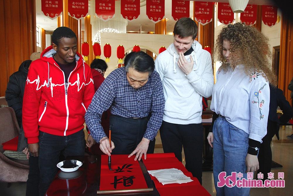 1月30日、威海南海新区江南城コミュニティによる開催された「新年を迎えて春聯を書き、祝福を送る」イベントの中、外国留学生は春聯を書いていた。<br/>