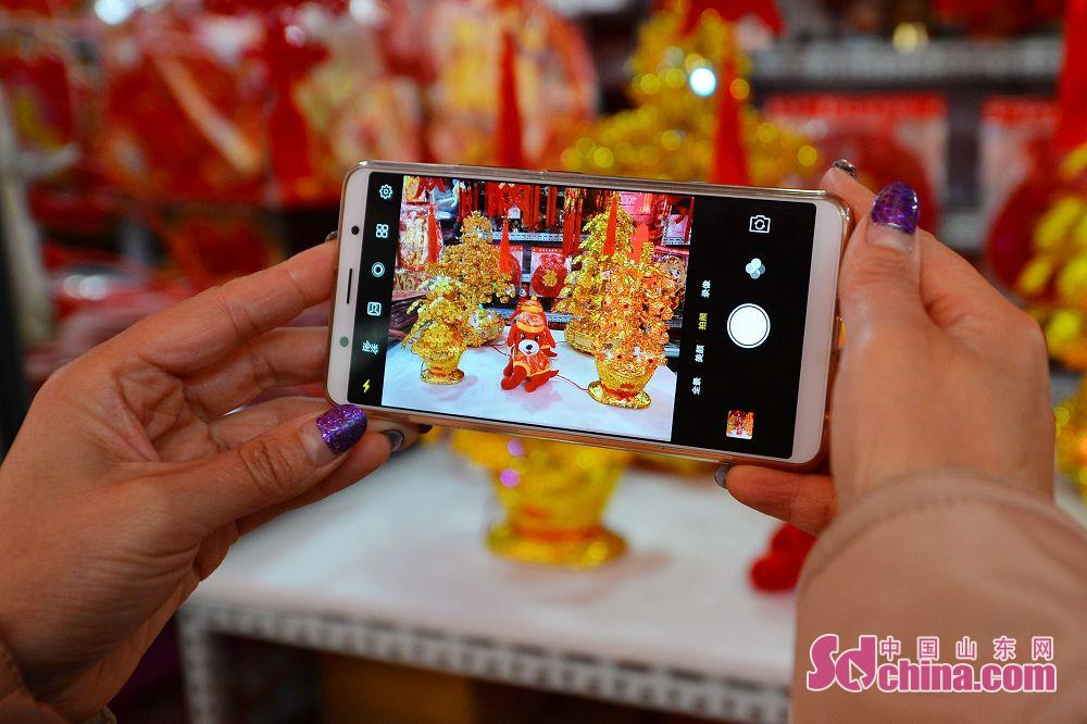 <br/>  市民用手机拍摄春节饰品。