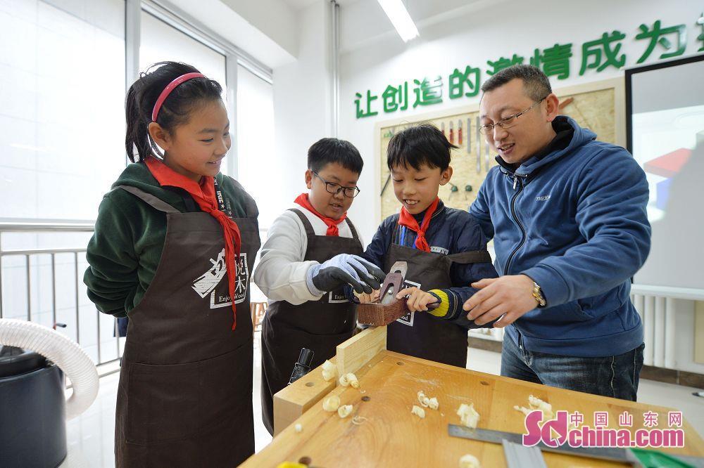 <br/>  科学老师在木艺小创客活动中教授孩子们学习使用木工工具。<br/>