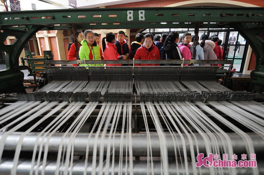 <br/>  学生在纺织博物馆遗址公园参观了解纺织设备工作流程,感受青岛百年纺织历史。
