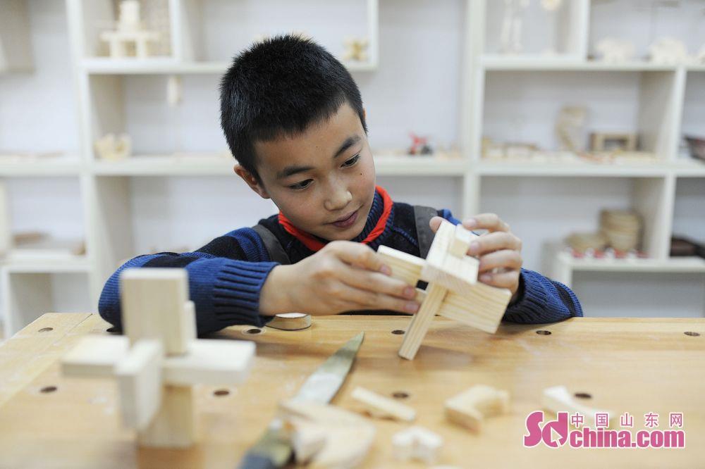 <br/>  学生在木艺小创客活动中学习制作鲁班锁。<br/>