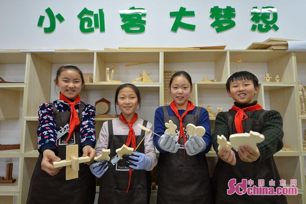 <br/>  学生展示木艺小创客活动上自己动手制作出的木工工艺品。