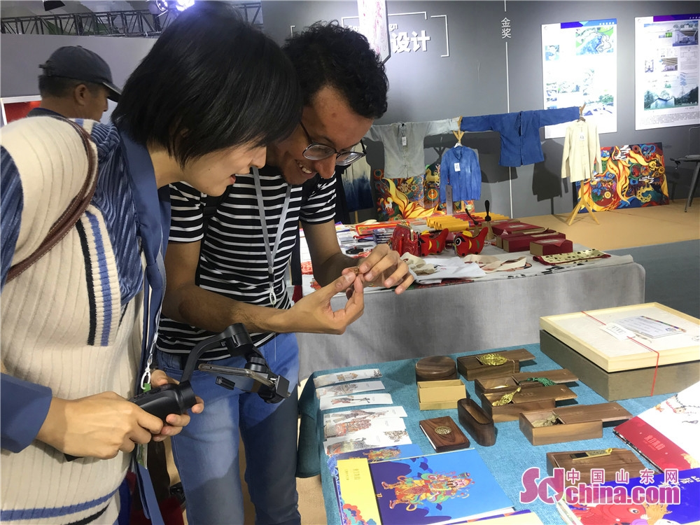 A foreign visitor views artworks during the 7th Shandong Cultural Industries Fair (SDCIF) held in Jinan, Shandong Province on October 11, 2018. During the five-day fair, a cultural feast made up of &ldquo;culture plus technology&rdquo;, &ldquo;culture plus tourism&rdquo;, &ldquo;culture plus finance&rdquo;, &ldquo;culture plus creativity&rdquo;, &ldquo;culture plus industry&rdquo; and other elements will be presented to the visitors.<br/>