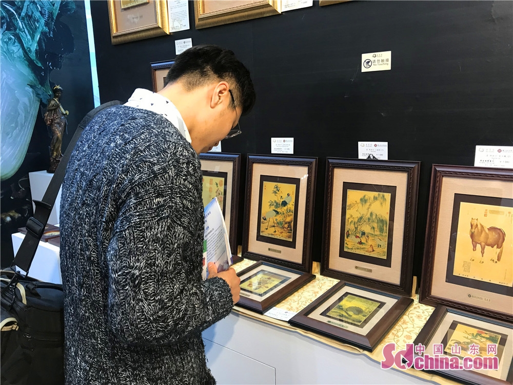 A Korean visitor views photo works during the 7th Shandong Cultural Industries Fair (SDCIF) held in Jinan, Shandong Province on October 11, 2018. During the five-day fair, a cultural feast made up of &ldquo;culture plus technology&rdquo;, &ldquo;culture plus tourism&rdquo;, &ldquo;culture plus finance&rdquo;, &ldquo;culture plus creativity&rdquo;, &ldquo;culture plus industry&rdquo; and other elements will be presented to the visitors.<br/>