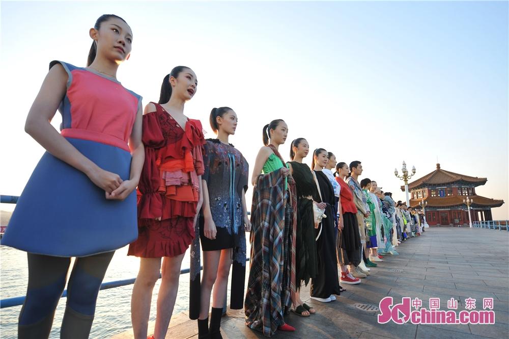 <br/>  2018年10月12日,来自全球五大洲25所时尚设计院校的学生在山东青岛百年栈桥上展示自己设计的代表性作品。