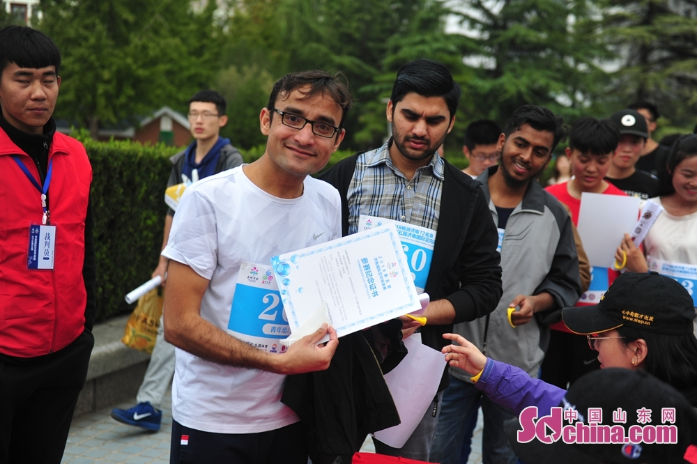 A foreign participant displays his certificate during the 5th Jinan International Spring-themed Orienteering in Jinan, Shandong Province on October 14, 2018. About 4,000 people from home and abroad participated in the race.<br/>