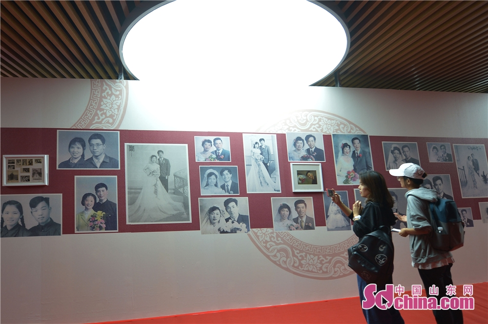 Visitors view wedding photos of different times during the 2018 Qingdao Wedding Cultural Week in Qingdao, a coastal city of Shandong Province on October 16, 2018. The six-day event aims to display the wedding characteristics of Qingdao and promote the development level of wedding industry.<br/>