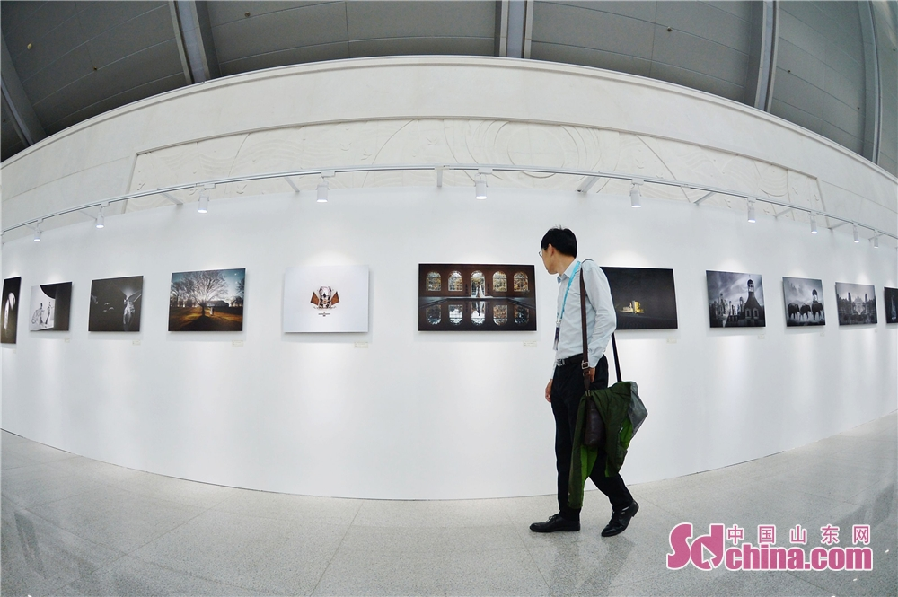 A visitor views photo works during the 2018 Qingdao Wedding Cultural Week in Qingdao, a coastal city of Shandong Province on October 16, 2018. The six-day event aims to display the wedding characteristics of Qingdao and promote the development level of wedding industry.<br/>