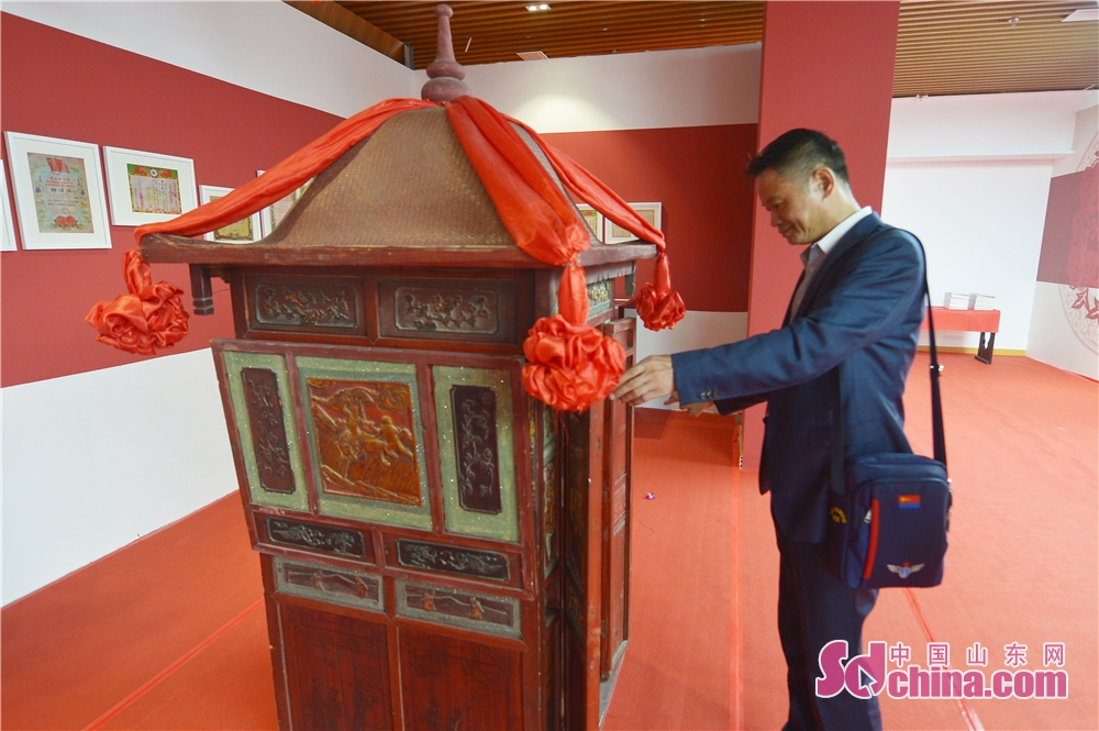 A visitor views the bridal sedan chair exhibited during the 2018 Qingdao Wedding Cultural Week in Qingdao, a coastal city of Shandong Province on October 16, 2018. The six-day event aims to display the wedding characteristics of Qingdao and promote the development level of wedding industry.<br/>