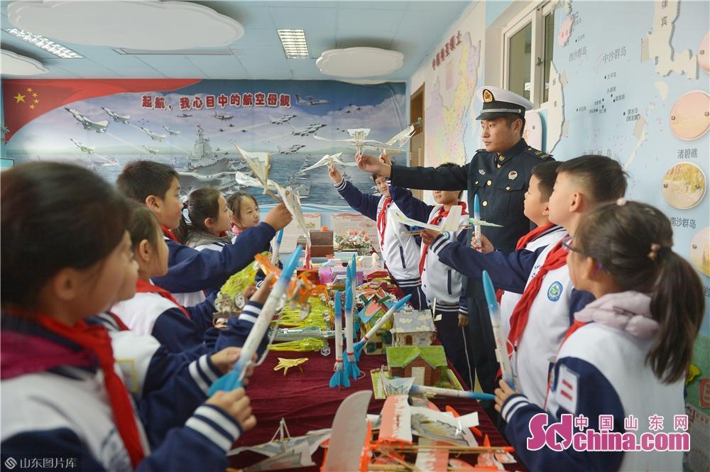 <br/>  2018年11月26日,青岛驻地海军战士与学生们互动,介绍各种航模知识。<br/>