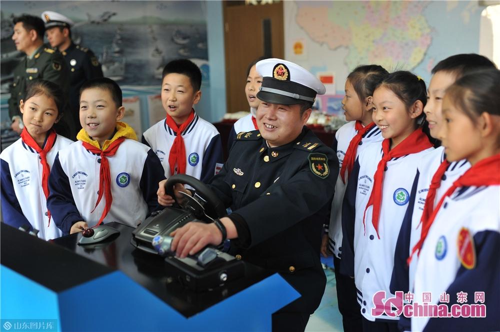 <br/>  2018年11月26日,青岛台湛路小学的学生们与驻地海军官兵一起通过大型驱逐舰模拟器模拟海战,增强国防意识。<br/>
