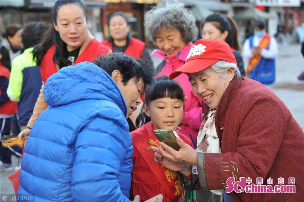 <br/>  2018年11月7日,山东省青岛市即墨路街道的老人与小学生志愿者一起合影留念。