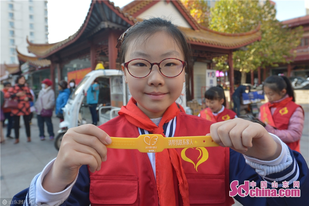 A girl shows a yellow band. These bands, with information of their names and their children's phone numbers, are expected to assist senior citizens in getting timely help and rescue in case of emergency.<br/>