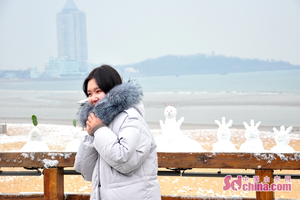 A visitor poses for a photo with the snow scenery on the sea in Qingdao, a coastal city of Shandong Province.<br/>