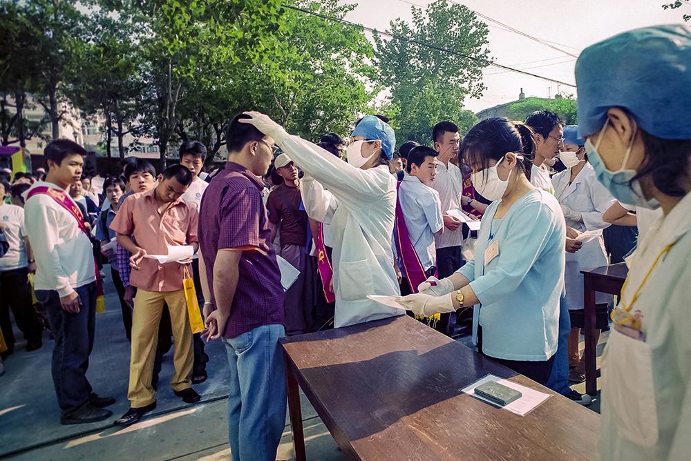 2003年6月,&amp;ldquo;非典&amp;rdquo;时期,准备进入烟台二中考场参加高考的学生们在接受体检。(孙强)<br/>