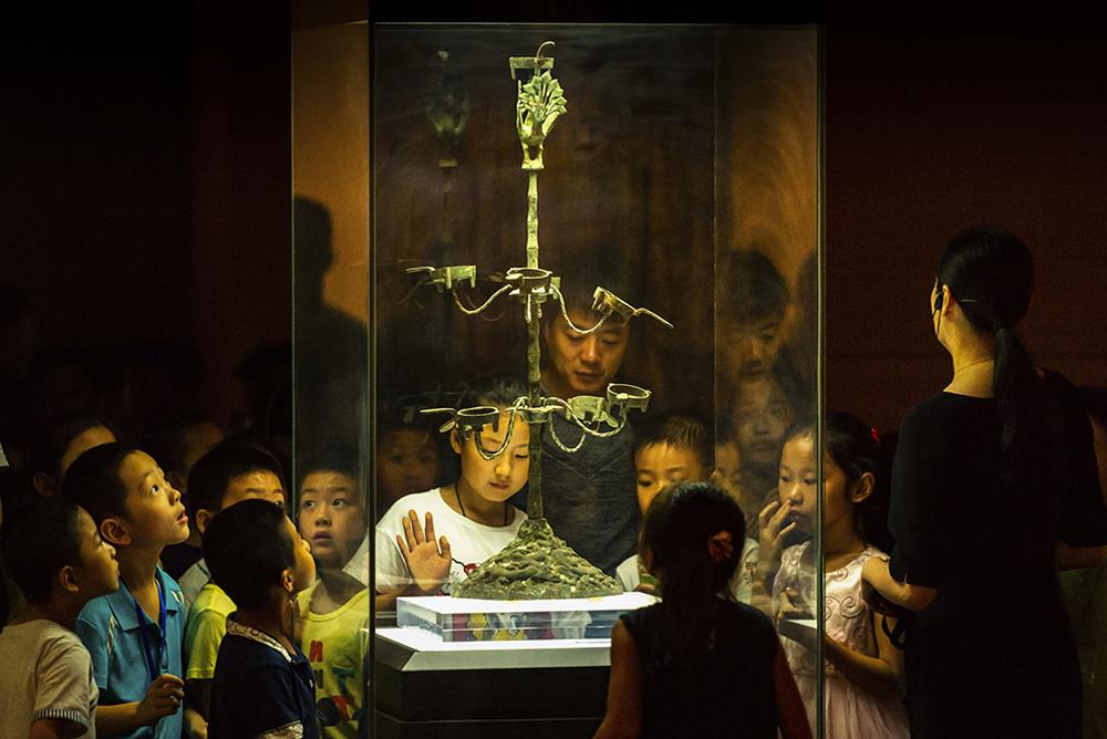 《相隔千年宛如初见》2018年暑假,小学生在烟台博物馆观看汉代九盏连枝灯。烟台市博物馆为国家一级馆,文物收藏量居全省第二位,是全国优秀等级博物馆。(李健)<br/>