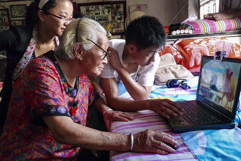 《八旬老太玩电脑》 招远市金岭镇寨里村85岁老人王淑芳,在孙子孙女的指导下用电脑与在黑龙江的女儿视频聊天。(杨波)<br/>