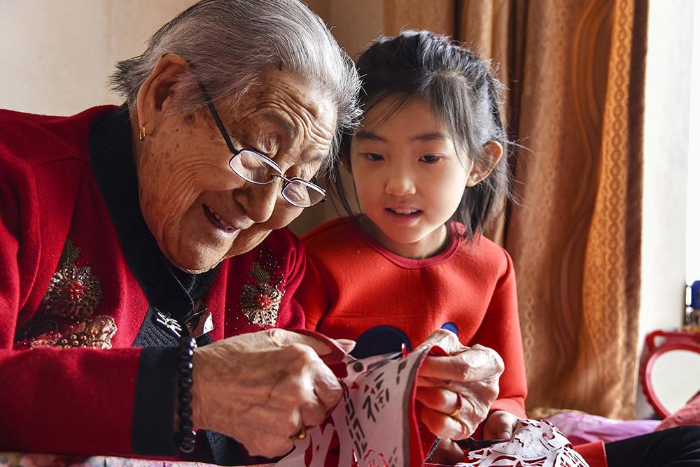 2017年,福山区103岁的林桂茂老人在向小徒弟传授剪纸技艺。烟台剪纸是一门古老的传统民间艺术,距今已有七八百年的历史,2008年入选第一批国家级非物质文化遗产扩展项目名录。(卢艳)<br/>