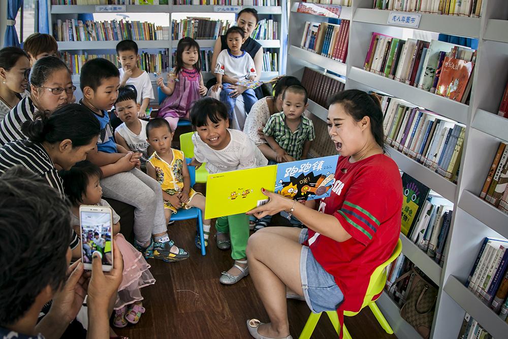 2018年7月2日,文化志愿者在烟台市图书馆的流动图书车里给小朋友们讲故事。 (李俊杰)<br/>