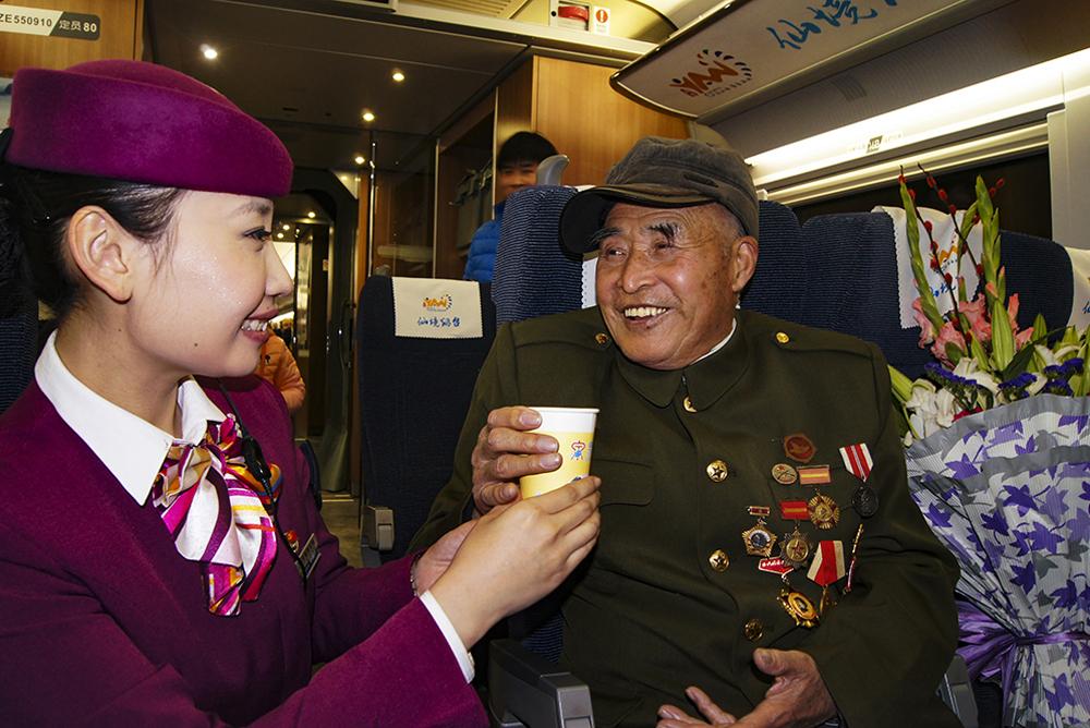 2014年12月28日,青烟威荣城际铁路正式开通运营。牟平革命老兵许家绥,应邀体验青烟威荣城际铁路首次列车,受到乘务员的热情接待。(李苏适)<br/>