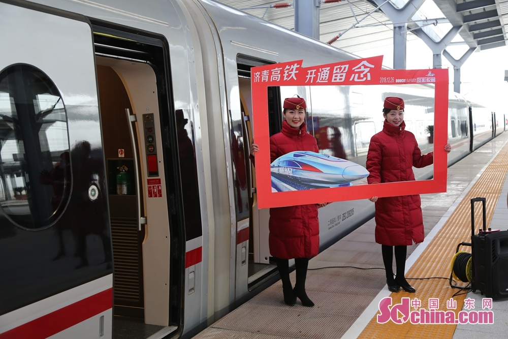 Two train attendants pose for photos with the bullet train in Jinandong Railway Station in Jinan, east China&amp;rsquo;s Shandong Province on December 26, 2018. Jinan-Qingdao High-speed Railway opens today, cutting down the running time of the fastest train from Jinan to Qingdao to 1 hour and 40 minutes.<br/>