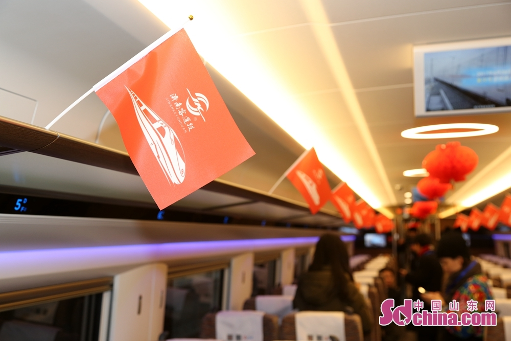 Passengers get on the bullet train in Jinandong Railway Station in Jinan, east China's Shandong Province on December 26, 2018. Jinan-Qingdao High-speed Railway opens today, cutting down the running time of the fastest train from Jinan to Qingdao to 1 hour and 40 minutes.