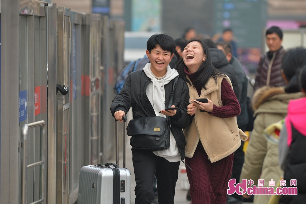 Two passengers chat on their way to board the train at the Qingdao Railway Station to in Qingdao, Shandong Province, on Feb. 11, 2018. A Spring Festival, or better known as Chinese Lunar New Year, is the most important festival for all Chinese, which has a history of more than 4,000 years. It is an occasion for home returning, New Year goods preparing, celebrating, and foremost, family reunion. (Sdchina.com/Wang Haibin)<br/>