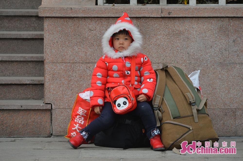 <br/><br/>  2月9日,一名小朋友在青岛火车站守在行李旁等待乘车。<br/>