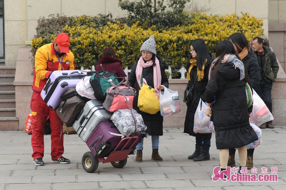 A railway worker helps passengers to carry luggage before they board the train at the Qingdao Railway Station to in Qingdao, Shandong Province, on Feb. 11, 2018. A Spring Festival, or better known as Chinese Lunar New Year, is the most important festival for all Chinese, which has a history of more than 4,000 years. It is an occasion for home returning, New Year goods preparing, celebrating, and foremost, family reunion. (Sdchina.com/Wang Haibin)<br/>