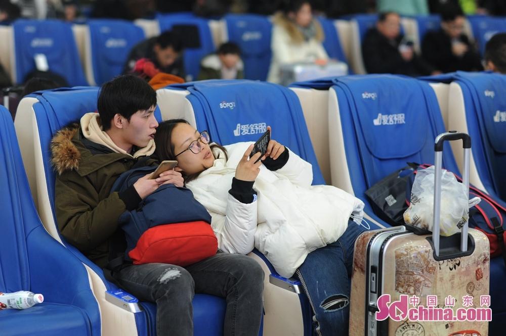 <br/><br/>  2月9日,在青岛火车站候车室,人们拿着手机打发候车时间。<br/>