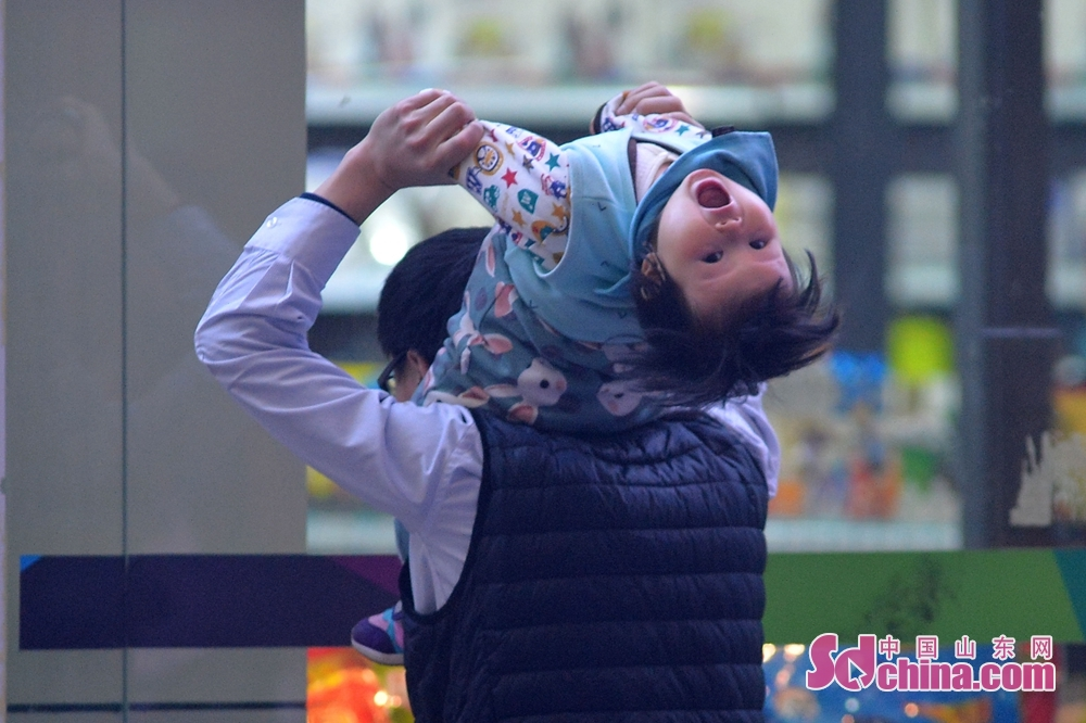 A passenger holds her child to board the train at the Qingdao Railway Station to in Qingdao, Shandong Province, on Feb. 11, 2018. A Spring Festival, or better known as Chinese Lunar New Year, is the most important festival for all Chinese, which has a history of more than 4,000 years. It is an occasion for home returning, New Year goods preparing, celebrating, and foremost, family reunion. (Sdchina.com/Wang Haibin)