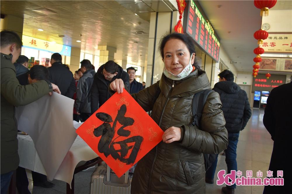 <br/>  旅客们拿着书法家书写的对联、福字准备回家。