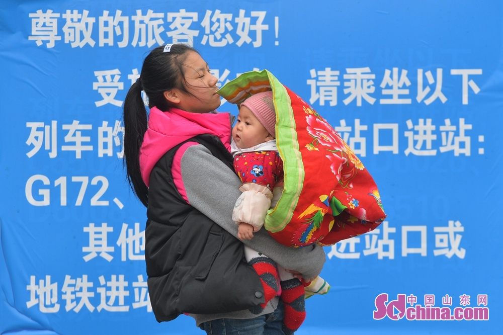 A passenger holds her child to board the train at the Qingdao Railway Station to in Qingdao, Shandong Province, on Feb. 11, 2018. A Spring Festival, or better known as Chinese Lunar New Year, is the most important festival for all Chinese, which has a history of more than 4,000 years. It is an occasion for home returning, New Year goods preparing, celebrating, and foremost, family reunion. (Sdchina.com/Wang Haibin)<br/>