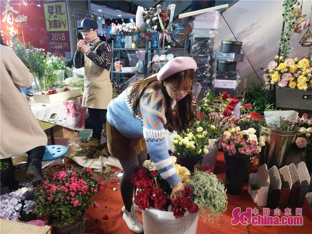 <br/>  一名店员在整理店内的鲜花。<br/>