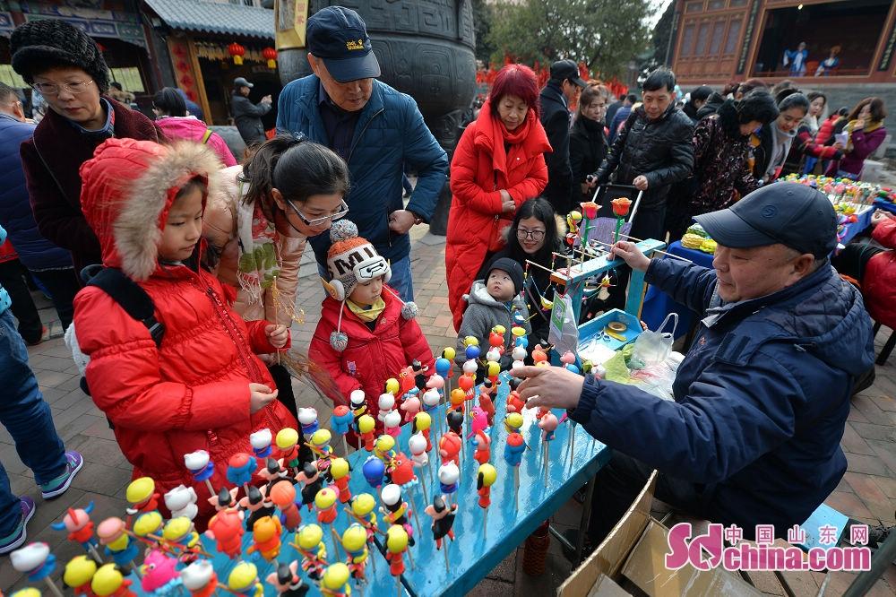 <br/>  孩子们在青岛市新正民俗文化庙会上围观面人师傅制作的玩偶。<br/>
