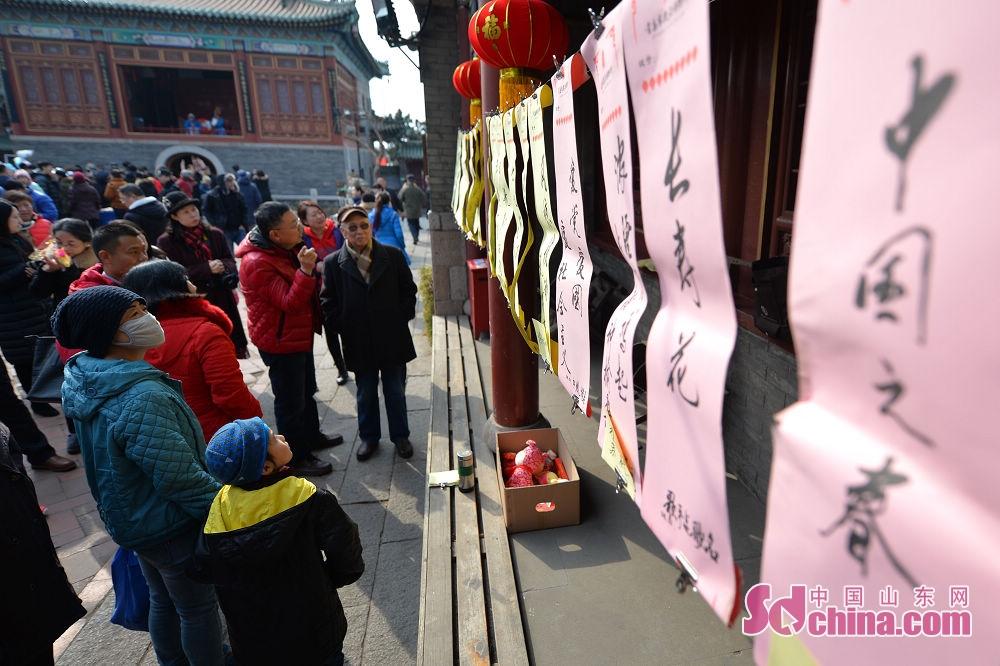 <br/>  市民在青岛市新正民俗文化庙会上猜灯谜。<br/>