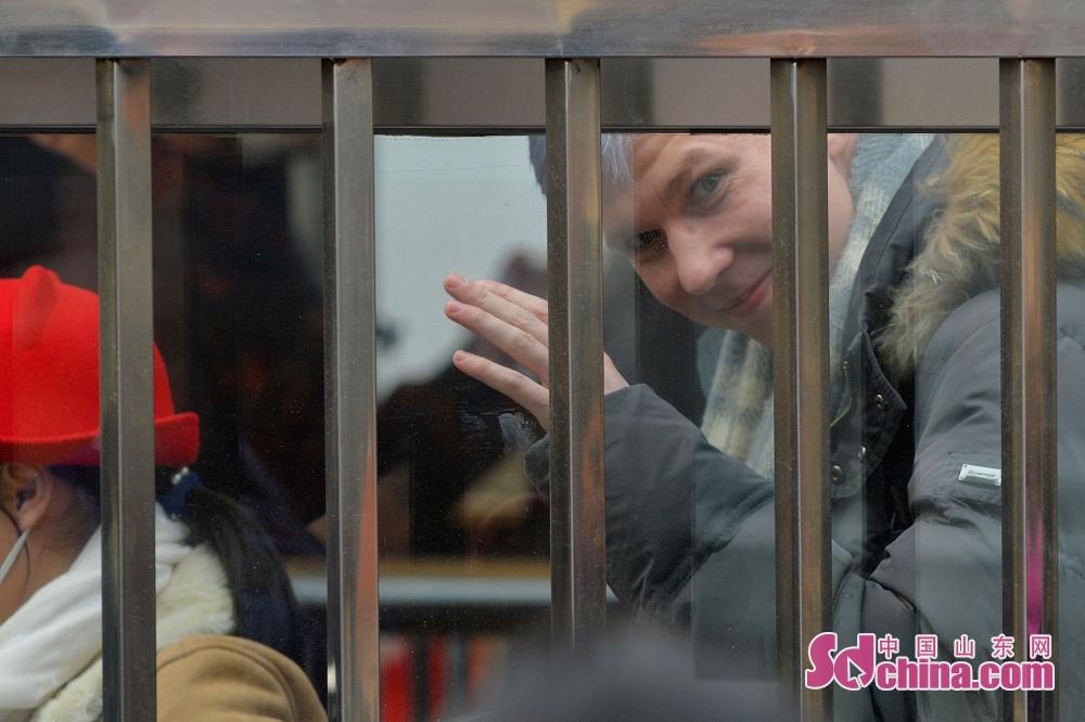 한 외국 승객은 기차역에서 배웅하는 친구와 손혼들어 작별하고 있다.<br/>