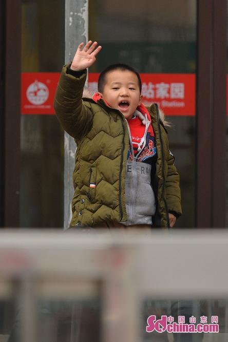 한 어린이는 기차역에서 배웅하는 친구들과 작별을 고하고 있다.<br/>