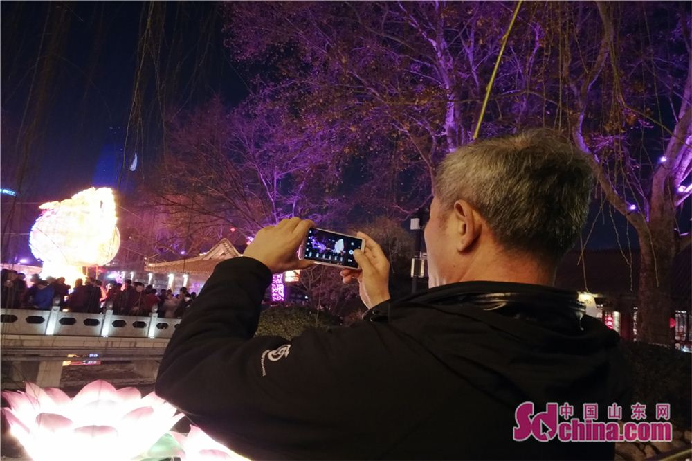 A visitor takes a picture of a set of lanterns at Baotu Spring scenic spot in Jinan, capital of Shandong Province, on Feb. 24, 2018. The lantern show will last up to March 7 to celebrate the upcoming Lantern Festival. (Sdchina.com/Zhang Yuanyuan)<br/>