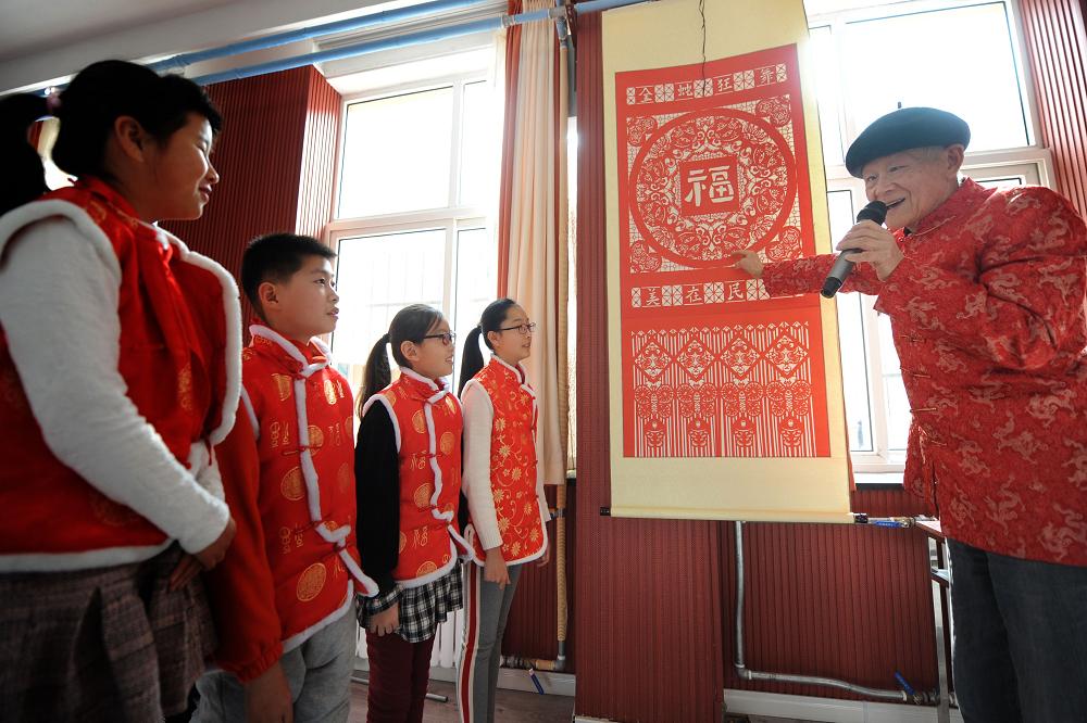 <br/>  民间剪纸艺人为学生们讲解传统剪纸文化。