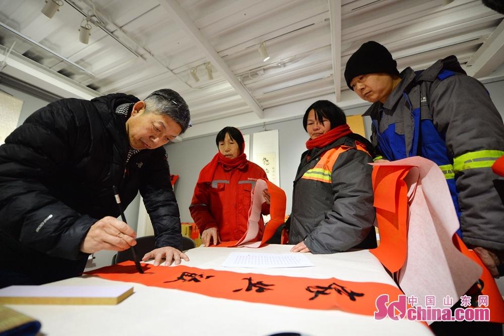 <br/><br/>  2018年2月2日,在青岛市新100创意文化产业园,艺术家为环卫工人义务书写春联。<br/>