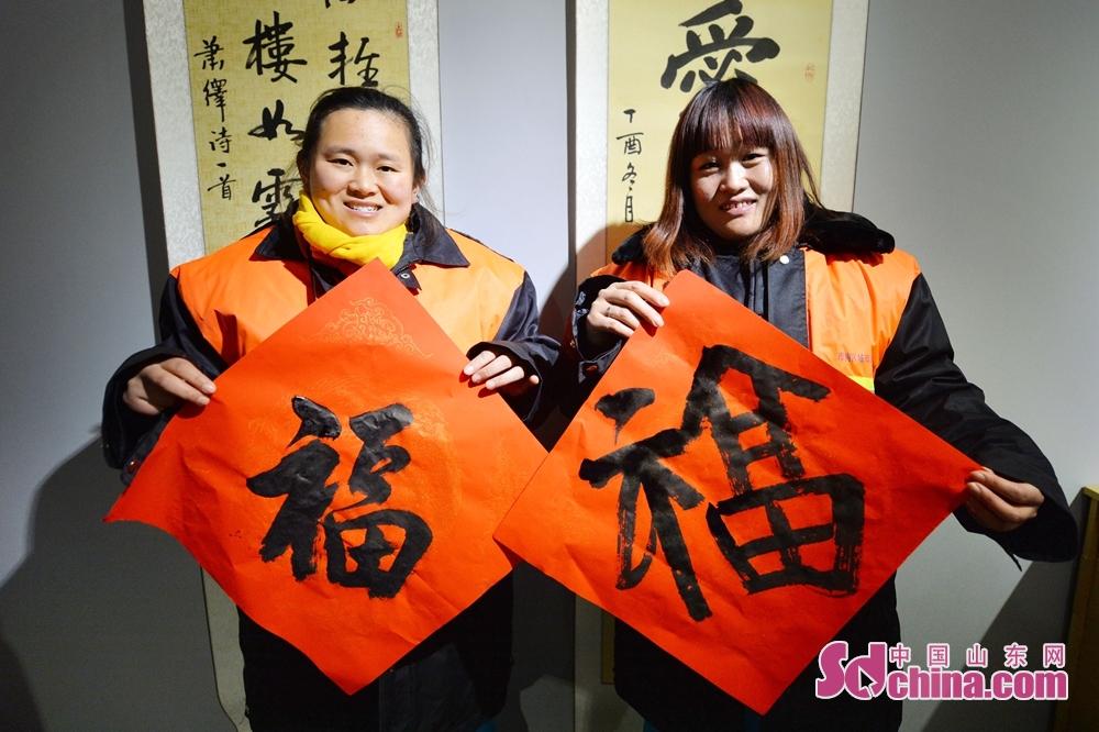 <br/><br/>  2018年2月2日,在青岛市新100创意文化产业园,两名环卫工人拿到艺术家书写的福字门贴。<br/>