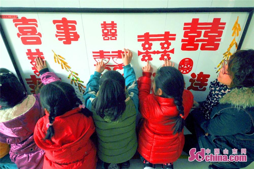 <br/>  沂源县南鲁山镇中心小学的小朋友在老师的指导下观看窗花展。